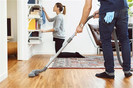 Low section of man vacuuming floor while woman cleaning shelves in background at home Stock Photo - Premium Royalty-Free, Code: 698-08081787