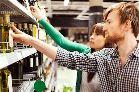 shop - Young couple analyzing products in supermarket Stock Photo - Premium Royalty-Free, Code: 698-08081806
