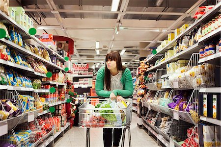 Young woman leaning on shopping cart at supermarket aisle Stock Photo - Premium Royalty-Free, Code: 698-08081807
