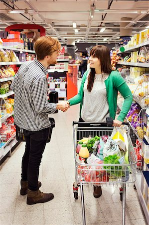 Man and woman shaking hands at supermarket aisle Stock Photo - Premium Royalty-Free, Code: 698-08081808