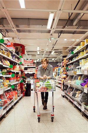 Young man leaning on shopping cart at supermarket aisle Stock Photo - Premium Royalty-Free, Code: 698-08081809