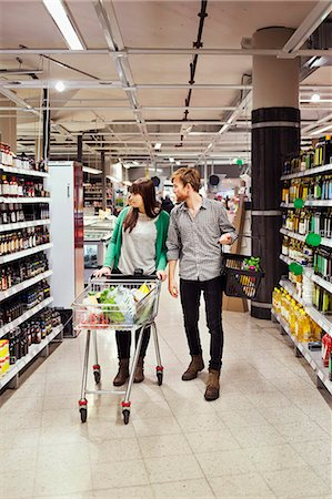 Young couple walking while shopping in supermarket Stock Photo - Premium Royalty-Free, Code: 698-08081803