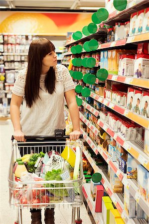selecting - Woman looking at products while shopping in supermarket Stock Photo - Premium Royalty-Free, Code: 698-08081814