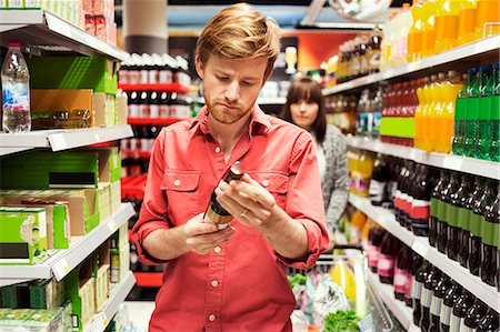 shop - Man reading label on bottle while shopping in supermarket Stock Photo - Premium Royalty-Free, Code: 698-08081815
