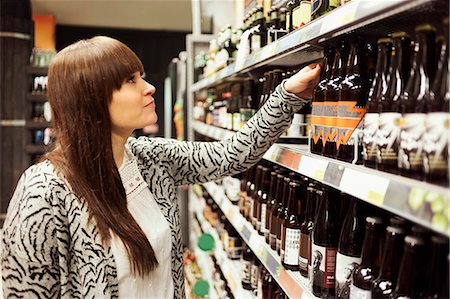 Young woman selecting bottle in supermarket Stock Photo - Premium Royalty-Free, Code: 698-08081816