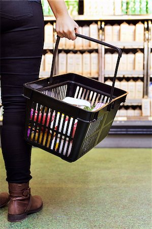 Low section of woman carrying basket in supermarket Stock Photo - Premium Royalty-Free, Code: 698-08081817