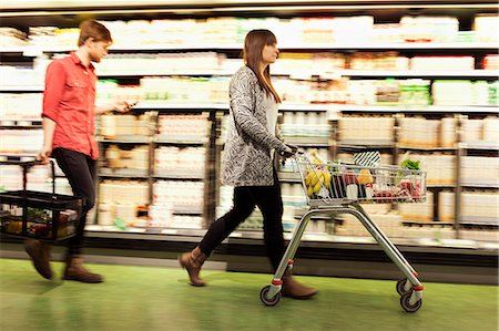 pushing - Young couple walking by shelves at supermarket Stock Photo - Premium Royalty-Free, Code: 698-08081818