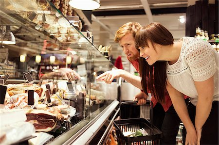 Young couple choosing fresh meat at supermarket Stock Photo - Premium Royalty-Free, Code: 698-08081812