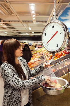 Woman looking at weight scale while weighing apples at supermarket Stock Photo - Premium Royalty-Free, Code: 698-08081826