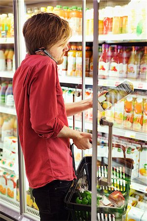 Side view of man answering mobile phone while shopping at freezer section in supermarket Stock Photo - Premium Royalty-Free, Code: 698-08081821