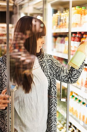 Young woman reading label on juice at refrigerated section in supermarket Stock Photo - Premium Royalty-Free, Code: 698-08081822