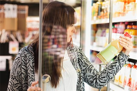 Young woman reading label on juice bottle at refrigerated section in supermarket Stock Photo - Premium Royalty-Free, Code: 698-08081823