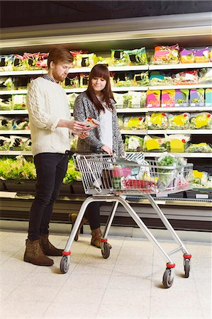 Young couple analyzing product in supermarket Stock Photo - Premium Royalty-Free, Code: 698-08081836