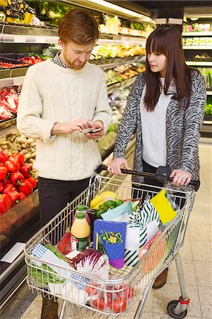 Young couple using mobile phone while buying groceries at supermarket Stock Photo - Premium Royalty-Free, Code: 698-08081830