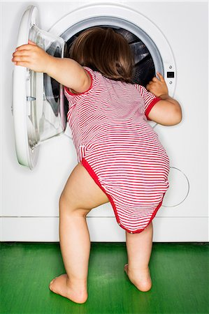 Rear view of baby girl peeking into washing machine at home Stock Photo - Premium Royalty-Free, Code: 698-08170849