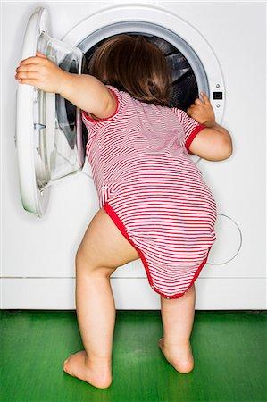 Rear view of baby girl peeking into washing machine at home Stock Photo - Premium Royalty-Free, Code: 698-08170849