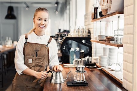 europe coffee shop - Portrait of happy female barista standing at counter in coffee shop Stock Photo - Premium Royalty-Free, Code: 698-08170868