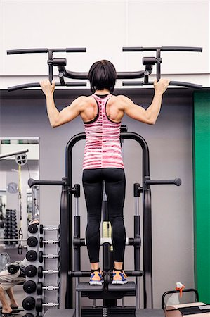 Rear view of sporty woman exercising at health club Stock Photo - Premium Royalty-Free, Code: 698-08170863