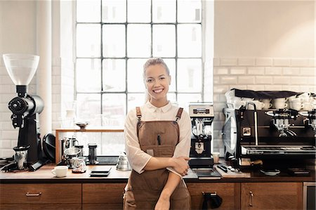 Portrait of happy female barista standing by counter in coffee shop Stock Photo - Premium Royalty-Free, Code: 698-08170878