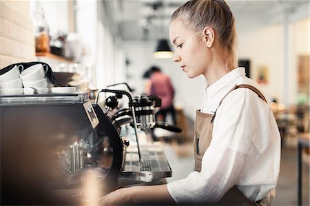 Side view of young female barista using espresso maker at cafe Stock Photo - Premium Royalty-Free, Code: 698-08170870