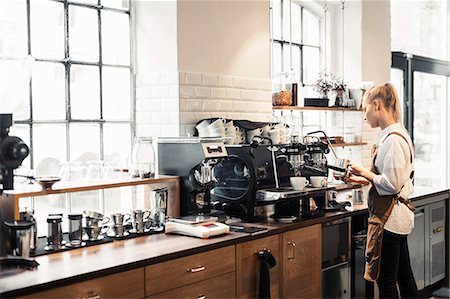 europe coffee shop - Female barista using coffee machine at cafe Stock Photo - Premium Royalty-Free, Code: 698-08170872