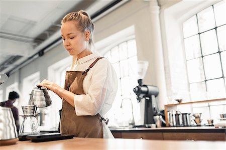 europe coffee shop - Female barista pouring boiling water in coffee filter at cafe Stock Photo - Premium Royalty-Free, Code: 698-08170884