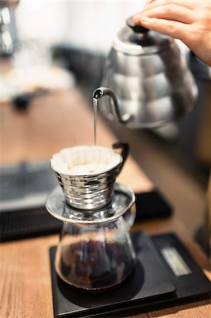 Cropped image of barista pouring boiling water in coffee filter at counter Stock Photo - Premium Royalty-Free, Code: 698-08170885