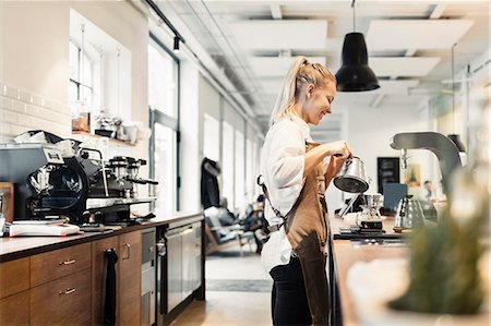 Side view of female barista preparing coffee at counter Stock Photo - Premium Royalty-Free, Code: 698-08170886