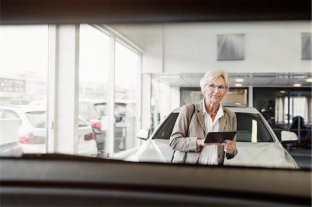 Senior businesswoman with digital tablet looking at car in store Stock Photo - Premium Royalty-Free, Code: 698-08170900