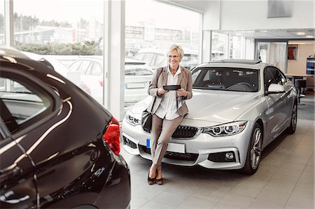 Happy businesswoman with digital tablet looking at car in store Stock Photo - Premium Royalty-Free, Code: 698-08170902