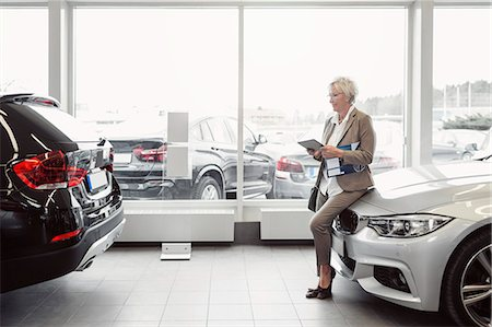 Full length of businesswoman with digital tablet sitting on car at store Stock Photo - Premium Royalty-Free, Code: 698-08170903