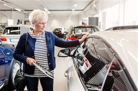 Senior woman admiring car in dealership store Stock Photo - Premium Royalty-Free, Code: 698-08170912