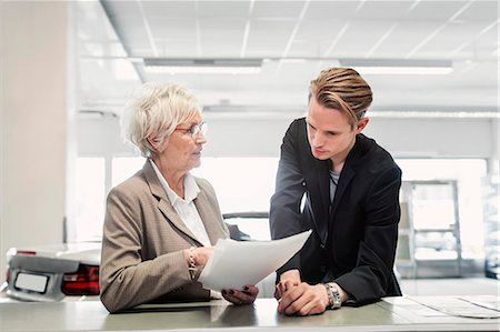 Two sales colleagues discussing documents at car dealership Stock Photo - Premium Royalty-Free, Code: 698-08170932
