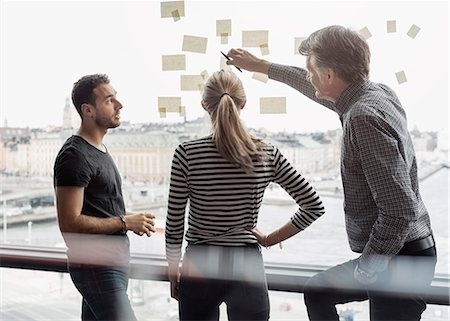 Businessman explaining adhesive notes to colleagues in office Stock Photo - Premium Royalty-Free, Code: 698-08170954