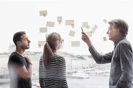 Business people discussing over adhesive notes stuck to glass window Stock Photo - Premium Royalty-Free, Code: 698-08170957