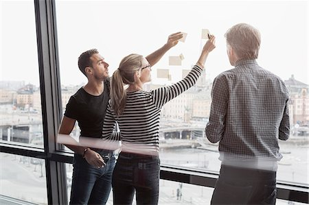 Business people discussing over adhesive notes stuck to glass window Stock Photo - Premium Royalty-Free, Code: 698-08170958