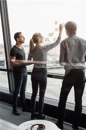 strategy - Business colleagues discussing over adhesive notes stuck to glass window Stock Photo - Premium Royalty-Free, Code: 698-08170959