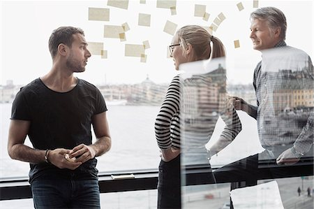 self adhesive note - Business colleagues discussing by glass window in office Stock Photo - Premium Royalty-Free, Code: 698-08170953