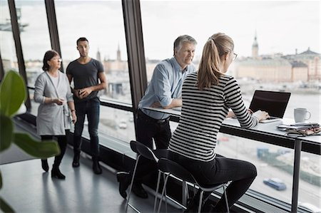 Business people discussing by window in office Stock Photo - Premium Royalty-Free, Code: 698-08170977
