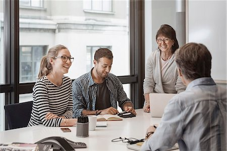 Happy senior businesswoman discussing with colleagues in board room Stock Photo - Premium Royalty-Free, Code: 698-08170971