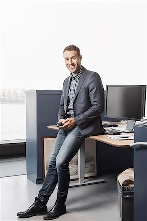 Full length portrait of confident businessman leaning on desk in office Stock Photo - Premium Royalty-Free, Code: 698-08170987