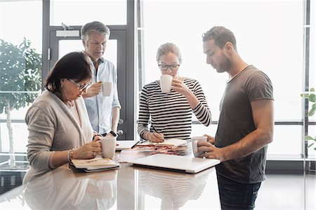 Business people working while having coffee at counter in office cafe Stock Photo - Premium Royalty-Free, Code: 698-08170983