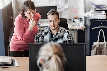 Colleagues using computer at desk in office Stock Photo - Premium Royalty-Free, Code: 698-08170996