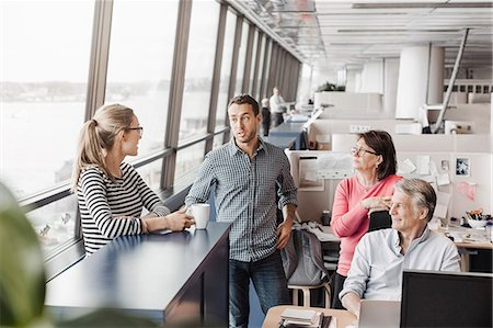 Business people discussing at cubicle in office Stock Photo - Premium Royalty-Free, Code: 698-08170992