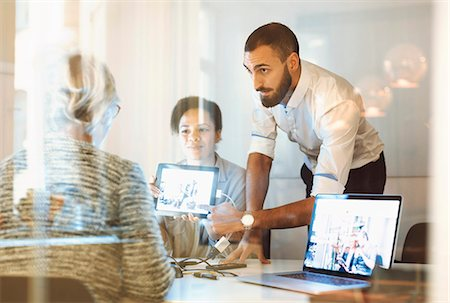 Business people giving presentation to colleague in office Stock Photo - Premium Royalty-Free, Code: 698-08171015