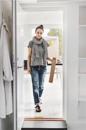 Full length of female architect walking towards doorway at home Stock Photo - Premium Royalty-Free, Code: 698-08171026