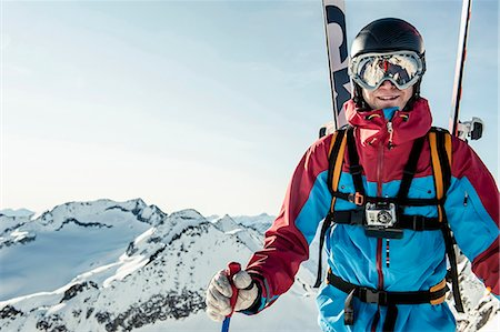 Portrait of smiling male skier standing on snowcapped mountain against clear sky Stock Photo - Premium Royalty-Free, Code: 698-08226276