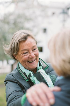 Happy senior woman talking to friend at park Stock Photo - Premium Royalty-Free, Code: 698-08226279