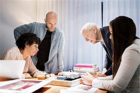Business team discussing over model in board room Stock Photo - Premium Royalty-Free, Code: 698-08226293