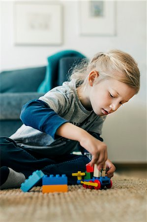 Girl making toy car with blocks while sitting on floor at home Stock Photo - Premium Royalty-Free, Code: 698-08226318